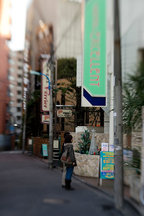 Satomi, 32, a web designer from Tokyo walks in the Shinjuku district's entertainment area many popular Love Hotel are located  here. Nearly all meetings with  sex volunteers take place  in a love hotels.  Satomi went to the sex volunteers to lose her virginity. Satomi was in a relationship with a musician for seven years but could not have intercourse with her boyfriend. The couple broke up due to the sexual tensions. Satomi thought there was something wrong with her, so sought counseling with Kim and lost her virginity to a volunteer.