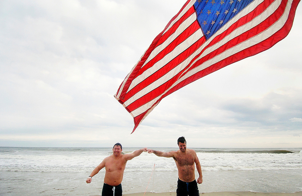 Brave participants Steve Kane (left) and Edward Amamea [cq] (right) both of Rumson quickly retreat from the cold waters of the Atlantic Ocean during the annual Polar Bear Plunge fundraiser held at Donovan's Reef Restaurant in Sea Bright on January 1, 2008.  More than 150 people gathered on the beach in Sea Bright for the fundraiser, held by Sons of Ireland.  The proceeds benefited Clean Ocean Action and Holiday Express. Photo essay from throughout the Jersey Shore, New Jersey