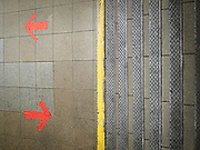 Steps leading to the subway platform.  Red arrows on the floor tile indicate the direction of pedestrian traffic.