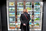 Nederland, Laren, 15-1-2016Een vrouw bekijkt de advertenties voor huizen die te koop staan. Hier in het Gooi is het aanbod van grote en kostbare huizen, landhuizen, erg groot. Huizen van meer dan een miljoen euro worden volop aangeboden.Foto: Flip Franssen