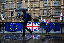© Licensed to London News Pictures. 02/04/2019. London, UK. A man shelters beneath an umbrella as he passes anti-Brexit protesters opposite Parliament. Prime Minister Theresa May is chairing a Cabinet meeting to try and agree a path forward with ministers after MPs voted to reject all alternatives to the Withdrawal Agreement for a second time. Photo credit: Rob Pinney/LNP