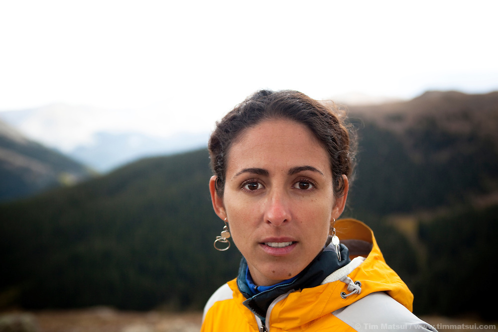 Portrait of a latina woman outdoors in the mountains lookint at the camera.