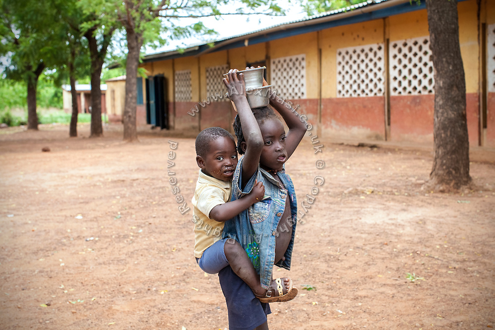 After having collected a nutritional meal available under the School Feeding Program run by the local NGO SEND, two pupils are walking in the courtyard of the small rural institution Hassana Ibrahim, 11, is attending in Boggu, Tamale, northern Ghana.