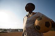 Boy holding football in Accra, Ghana, 2006.
