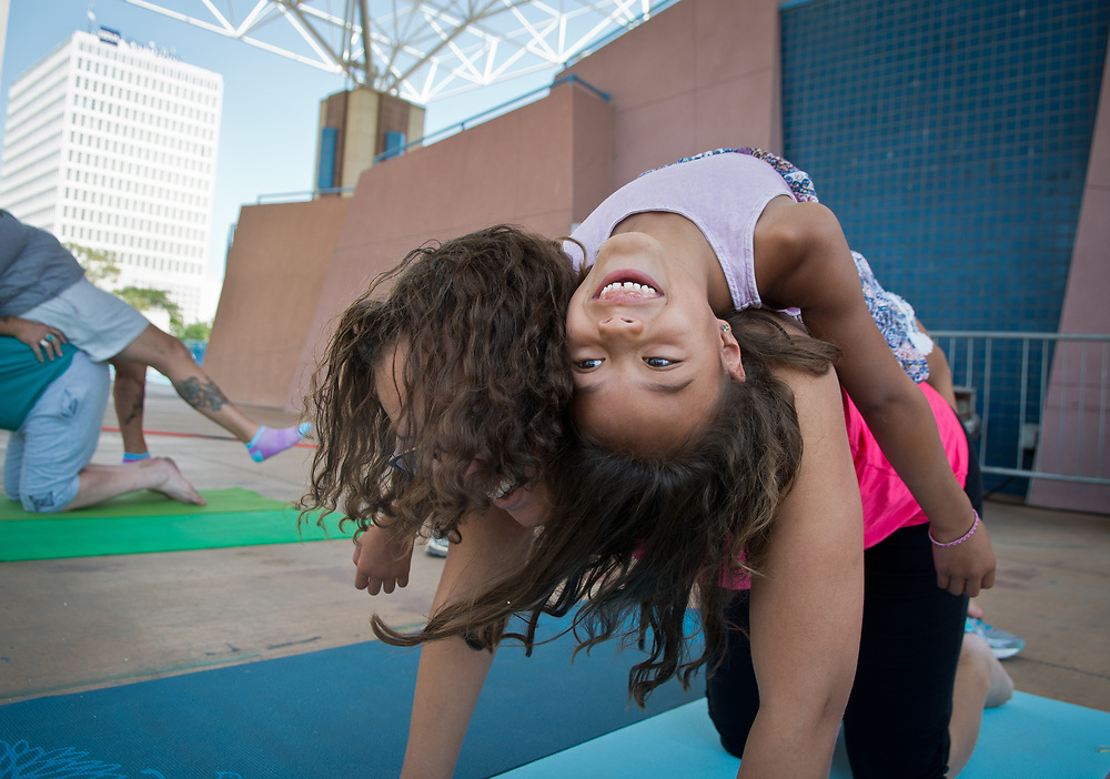 """mkb062717a/metro/Marla Brose --  Maelle Walker, 6, lays on her mom, Trisha Walker, during a family yoga class on the stage at Civic Plaza, Tuesday,  June 27, 2017, in Albuquerque, N.M. The 11 a.m. Tuesday yoga class, provided by Mi Vida Yoga, uses partner poses, designed but not limited for families. A traditional all-levels class is available at noon on Tuesday. Both class, for donation or free, will continue on Civic Plaza through summer. """"As you go through the postures, they represent challenges that appear through your day. And if you can breathe your way through the posture, it's training you to breathe through the challenging moments in life,"""" said Heather Smelser, owner of the yoga studio. (Marla Brose/Albuquerque Journal)"""