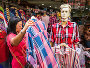 30 MAY 2013 - BANGKOK, THAILAND: A woman shops for shirts at Bobae Market in Bangkok. Bobae Market is a 30 year old famous for fashion wholesale and is now very popular with exporters from around the world. Bobae Tower is next to the market and  advertises itself as having 1,300 stalls under one roof and claims to be the largest garment wholesale center in Thailand.     PHOTO BY JACK KURTZ