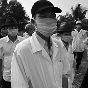 Vietnamese health officials, farmers and veteranarians watch as workers destroy thousands of chickens in a firepit in Long An Province, 50 kilometers outside Ho Chi Minh City, Friday 30 January 2004.