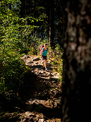 Women hiking through wood and rocks at Lac Blanc, Vosges, France
