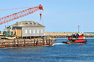 Barge moving a house with small pushy tug and crane loaded onboard being pulled by tugboat