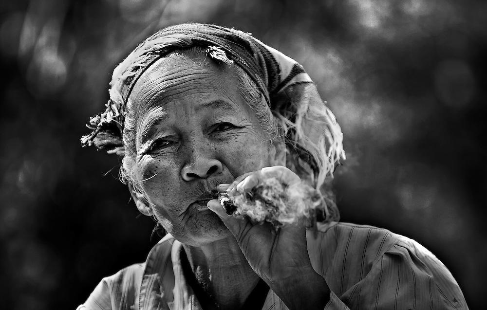 A Khamu woman smoking in a village on the Mekong river near Pak Beng, Laos.