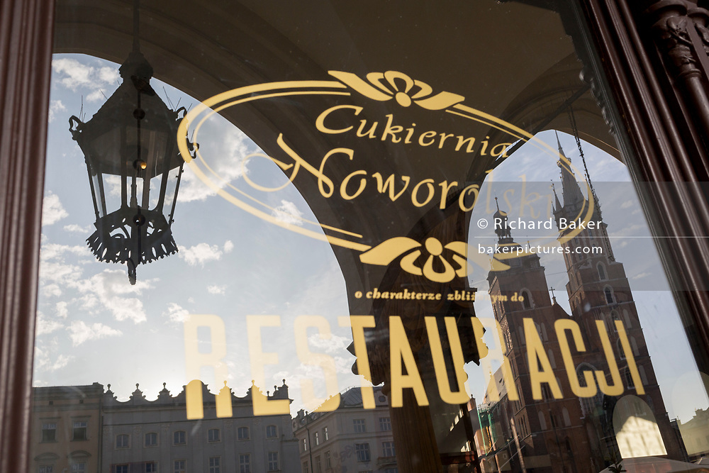 Reflections in the window of the Cukernia Noworolski cafe of the of the towers of Renaissance cloth hall and towers of the Church of St Mary on Rynek Glowny market square, on 23rd September 2019, in Krakow, Malopolska, Poland. Noworolski is a café located at the ground floor of the Cloth Hall, Kraków, Lesser Poland. It is considered one of the most famous cafes in Kraków.<br /> The tradition of the Noworolski dates to 19th century, through the opening of the renovated cafe under its current name took place in the years 1910-1912. It became popular among the elite of Kraków, with artists and professors but during the Nazi occupation the cafe was requisitioned and access allowed only to Germans. The family Noworolski again lost the place in 1949, when the cafe was nationalised by the communists and renamed. After the fall of communism, the café was returned to family ownership in 1992.
