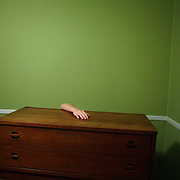 A woman's arm is seen over a piece of furniture in an otherwise empty room.