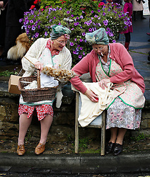 © Licensed to London News Pictures. <br /> 15/10/2016. <br /> Pickering, UK.  <br /> <br /> Two women dressed in period clothing do cleaning chores in Pickering during the North Yorkshire Moors Railway Wartime Weekend event. <br /> The annual event brings together re-enactors and enthusiasts along the length of the NYMR heritage steam railway line to recreate the feel of the war years of the 1940's. <br /> <br /> Photo credit: Ian Forsyth/LNP