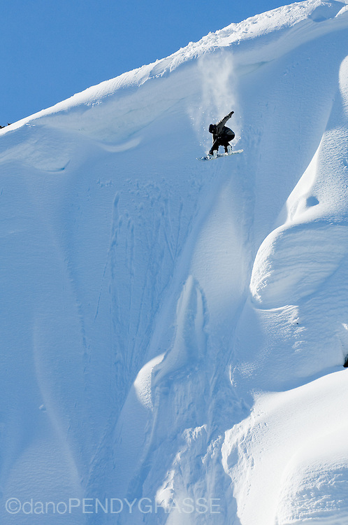 Professional Snowboarder Gabe Taylor airs into a snowy face while filming in the Coast Range, British Columbia, Canada.