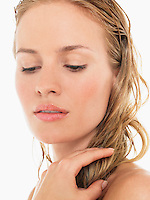 Young Blond Woman looking down and holding wet hair close up