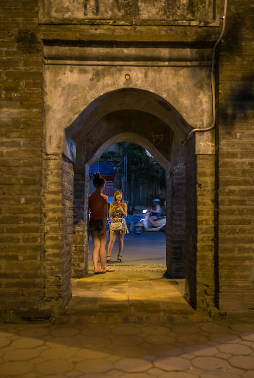 HANOI, VIETNAM - CIRCA SEPTEMBER 2014:  Young Vietnamese women at the Hoan Kiem Lake at night in Hanoi, Vietnam.