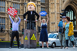 "© Licensed to London News Pictures. 03/09/2019. London, UK. Campaigners from Avaaz hold a photocall outside Parliament with a man dressed as Prime Minister Boris Johnson pushing the plunger on a ""No-Deal Bomb"", as two pedestrians watch on. MPs return from recess today and may vote on legislation to block a no deal exit from the European Union. Photo credit: Rob Pinney/LNP"