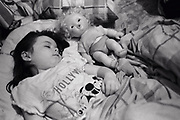 Little girl asleep in bed with her doll Newport South Wales