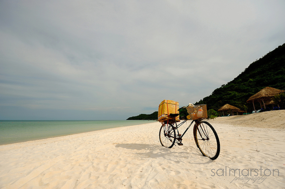 Old pedal bike with woven baskets stuck in sand on beautiful white sand beach
