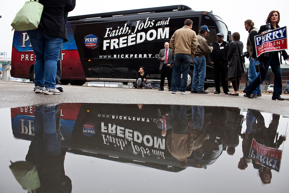 People wait outside the bus of Republican presidential candidate Rick Perry after a meet and greet at Drake on the Riverfront restaurant on Thursday, December 22, 2011 in Burlington, IA.