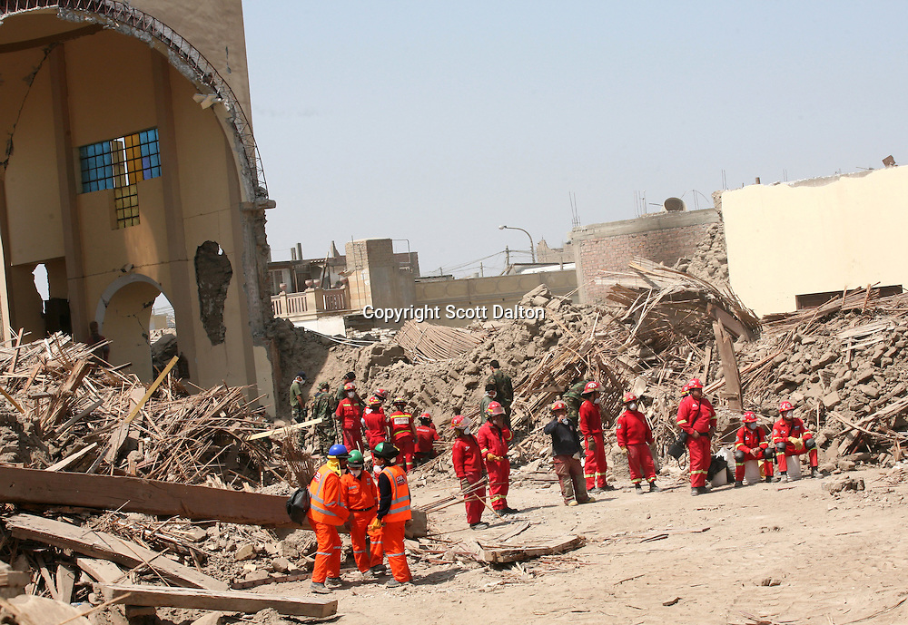 Workers stand amongst the ruins of a church that collapsed killing scores of people attending a mass at the time of a massive earthquake, in Pisco, Peru on Friday, August 17, 2007. The earthquake, that registered 8.0 on the Richter scale, left over five hundred people dead in Peru. (Photo/Scott Dalton).