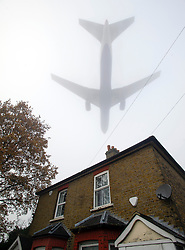 © London News Pictures. 11/12/2013. London, UK.  A plane approaching to land over a residential rooftop in heavy fog at Heathrow Airport in West London on December 11, 2013. Thick fog in southern England has caused travel disruption causing more than 80 flight cancellations at London's Heathrow and City airports. Photo credit: Ben Cawthra/LNP