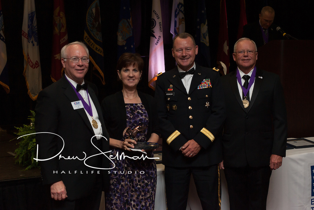 Sue Jordan (c.l.) receives the Pro Patria award on behalf of the Kansas City VA Hospital from Rear. Adm. (Ret.) Lee Metcalf (l.), MO ESGR State Chair, Brig. Gen. Martin Robinson (c.r.), Assistant Adjutant General Support for Missouri National Guard and Maj. Gen. (Ret.) Paul E. Mock (r.), National Chair for ESGR at the MO ESGR 2014 Annual Awards Dinner in Jefferson City on August 8, 2014.  ESGR, a DOD office, works employers to support and value the employment of National Guard and Reserve military. (MO ESGR / Drew Selman)