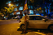 "Supporter of an independence for Catalonia in the street after the Catalan president Carles Puigdemont's speech broadcasted on a television screen at the Arc de Triomf (Triumphal Arch) in Barcelona on October 10, 2017. Catalonia's leader Carles Puigdemont said Tuesday he accepted the ""mandate of the people"" for the region to become ""an independent republic,"" but proposed suspending its immediate implementation to allow for dialogue.  10, 2017 in Barcelona, Spain. Christian Mantuano / OneShot"