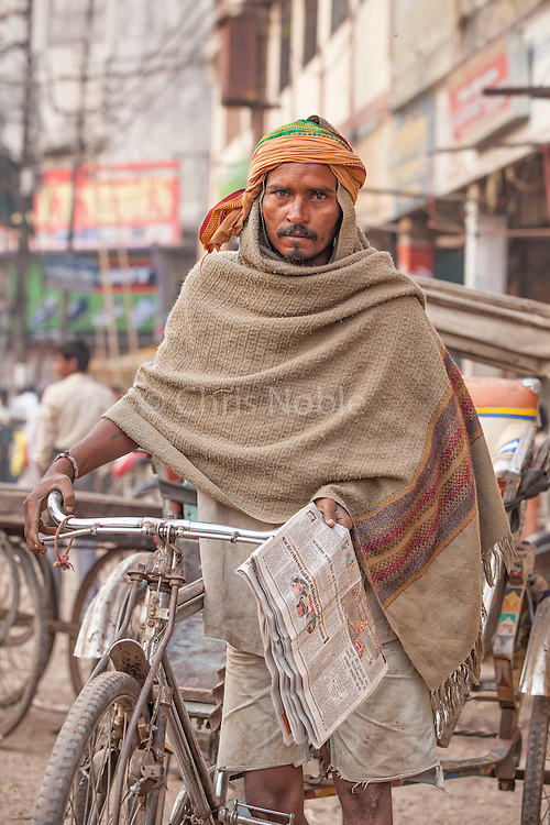 A bicycle rickshaw driver in the Old City of Varanasi India.