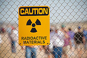 "Site Trinity, ground zero, on the White Sands Missile Range in S. New Mexico. Fence with radioactive sign and tourists during openhouse viisit. Site of the world's first atomic explosiion on August 6, 1945. The atomic bomb was developed by the Manhatten Project. The Manhattan Project refers to the effort during World War II by the United States, in collaboration with the United Kingdom, Canada, and other European physicists, to develop the first nuclear weapons. Formally designated as the Manhattan Engineering District (MED), it refers specifically to the period of the project from 1942-1946 under the control of the U.S. Army Corps of Engineers, under the administration of General Leslie R. Groves, with its scientific research directed by the American physicist J. Robert Oppenheimer. The project succeeded in developing and detonating three nuclear weapons in 1945: a test detonation on July 16 (the Trinity test) near Alamogordo, New Mexico; an enriched uranium bomb code-named ""Little Boy"" detonated on August 6 over Hiroshima, Japan; and a plutonium bomb code-named ""Fat Man"" on August 9 over Nagasaki, Japan. (http://en.wikipedia.org/wiki/Manhattan_Project)"