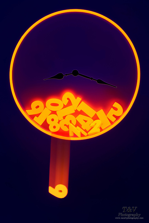 The glowing numbers of a clock have fallen with one number falling outside of the clock face. Blacklight photography.
