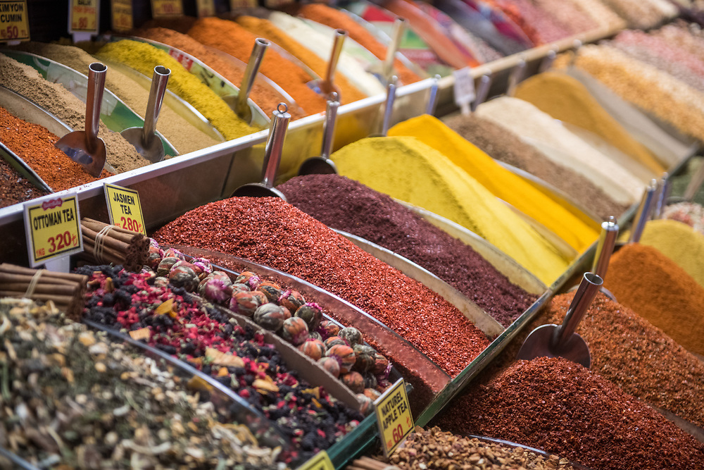Serve-yourself style bins full of a colorful array of spices and loose teas on display for sale at Istanbul Spice bazaar in Turkey