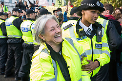 London, UK. 13 October, 2019. Police officers arrest a climate activist from Extinction Rebellion using Section 14 of the Public Order Act 1986 during a protest outside New Scotland Yard against tactics employed by police officers which impinge on the right to protest of disabled activists, including the confiscation of wheelchairs, wheelchair ramps, accessible toilets and tents. It was the seventh day of Extinction Rebellion International Rebellion protests.