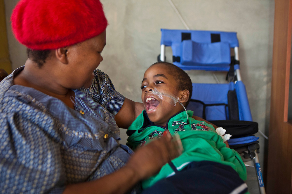 Clement, a South African boy, was born with Cerebral Palsy and lives at home with his mother Sbongile.  He is sitting on his mother's lap and they are playing together.  Clement is dependent on a wheelchair for mobility and requires feeding and medication through the nasal tube.  Durban, KaZulu Natal, South Africa.