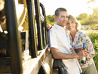 Adult couple standing by jeep man holding bottle of wine smiling
