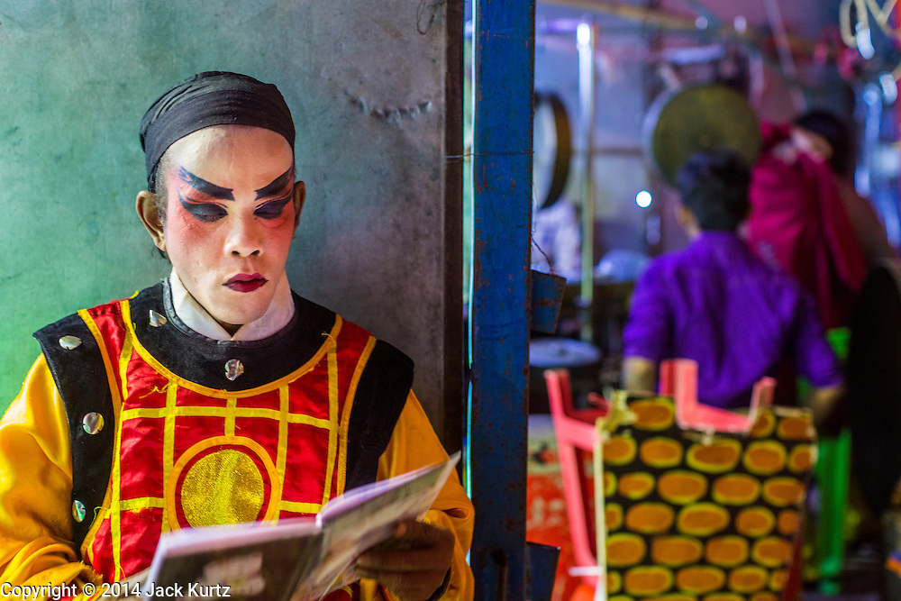 """25 JANUARY 2014 - BANG LUANG, NAKHON PATHOM, THAILAND: A performer backstage at a Chinese opera performance in a small town near Bang Luang, Nakhon Pathom, Thailand. Chinese opera was once very popular in Thailand, where it is called """"Ngiew."""" It is usually performed in the Teochew language. Millions of Chinese emigrated to Thailand (then Siam) in the 18th and 19th centuries and brought their cultural practices with them. Recently the popularity of ngiew has faded as people turn to performances of opera on DVD or movies. There are still as many 30 Chinese opera troupes left in Bangkok and its environs. They are especially busy during Chinese New Year when travel from Chinese temple to Chinese temple performing on stages they put up in streets near the temple, sometimes sleeping on hammocks they sling under their stage.     PHOTO BY JACK KURTZ"""