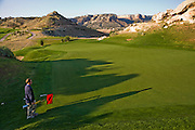 Bob Sorensen, an assistant golf course superintendent of The Golf Club at Redlands Mesa in Grand Junction, Colorado stands on the green during a routine inspection of the golf course. (Bob Sorensen is featured in the book What I Eat: Around the World in 80 Diets.) He played football at Mesa State College in Grand Junction and graduated with a degree in criminal justice. Just before he took a desk job in his chosen profession he decided that he didn't want a desk job and found one that requires his constant attendance of the great outdoors, at a golf course at the foot of the majestic Colorado National Monument.  He earned a second degree in turf management, supervises a small crew of greenskeepers, and coaches high school football at Palisade High School.