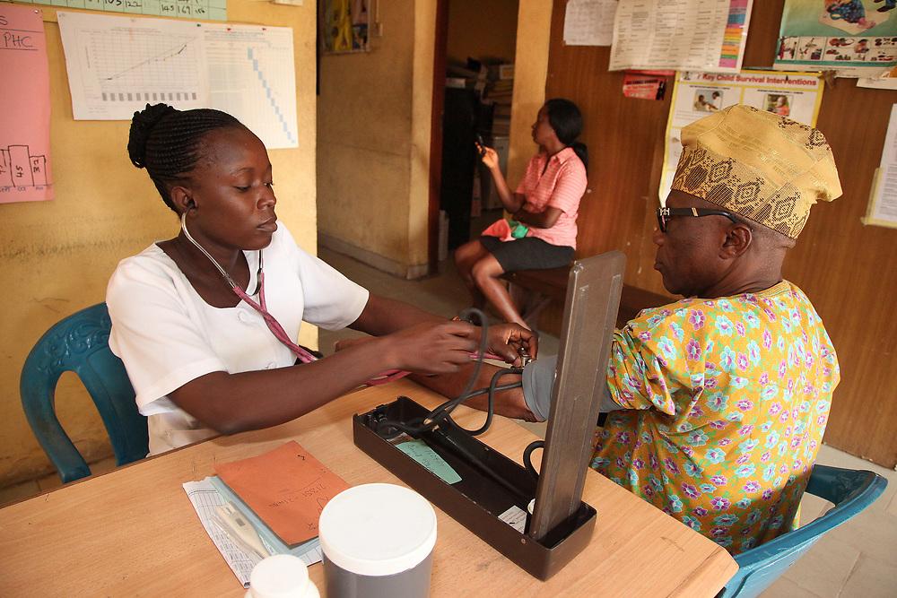 INDIVIDUAL(S) PHOTOGRAPHED: Adetona Olubunmi (left) and Hon Wale Ogundim (right). LOCATION: Ikeja Primary Health Care Center, Lagos, Nigeria. CAPTION: A nurse at the Ikeja Health Center takes the blood pressure of retired administrator Hon Wale Ogundim.