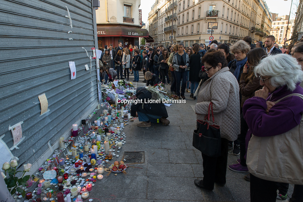Candles and flowers in front of Le Petit Cambodge, Paris.