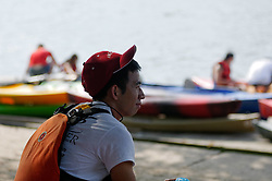A volunteer relaxes as he watches over festival-goers in the background embarking boats on the Schuylkill River. (Bastiaan Slabbers/for PhillyVoice)