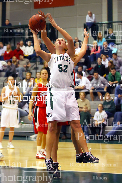 10 January 2009: A defender reaches over to block a shot being offered by Stacey Arlis. The Illinois Wesleyan Titans, ranked #1 in the latest USA Today/ESPN poll, take down the Lady Reds of Carthage and remain undefeated,  2-0 in the CCIW and over all to 12-0. This is the first time in the history of the Lady Titans Basketball they have been ranked #1 The Titans and Lady Reds played in the Shirk Center on the Illinois Wesleyan Campus in Bloomington Illinois.