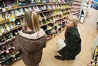 Laconia Boys and Girls Club executive director Cheryl Avery assists a young girl in picking out her new shoes made possible with a $400.00 grant from Payless Shoes of Gilford on Friday afternoon.   (Karen Bobotas/for the Laconia Daily Sun)