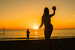 © Licensed to London News Pictures. 02/07/2018. Aberystwyth, UK. People play on the beach at sunset in Aberystwyth at the end of yet another hot and cloudless day, as the prolonged heatwave continues to dominate the weather over the UK. Photo credit: Keith Morris/LNP
