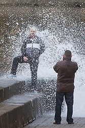 "© Licensed to London News Pictures. 09/11/2015. Bridlington, UK. A man poses for a photograph on the sea defences at the sea side town of Bridlington & gets caught out by a huge wave. The Yorkshire region was hit by severe gales this afternoon with winds up to 60mph. The Met Office warned West Yorkshire to expect gales and locally severe gales over high ground, with some ""very gusty"" winds to the east of high ground as well.<br /> Photo credit: Andrew McCaren/LNP"