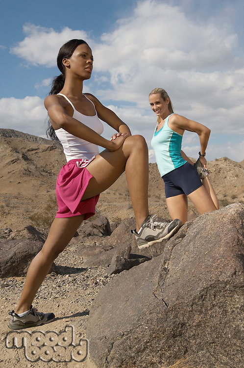 Two female joggers stretching in mountains