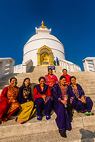 Nepali women sit for a portrait in front of the Shanti Stupa (The World Peace Pagoda) on Anadu Hill, above Pokhara, Nepal.