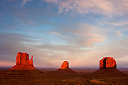 The Mittens and Merrick Butte are turned red as the sunset light hits these iconic rock formations on Monument Valley Navajo Tribal Park