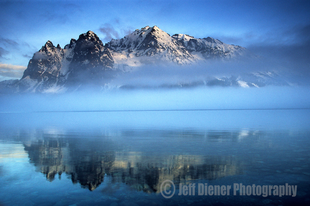 The Tetons are reflected in the glassy water of Jenny Lake, Grand Teton National Park, Jackson Hole, Wyoming.