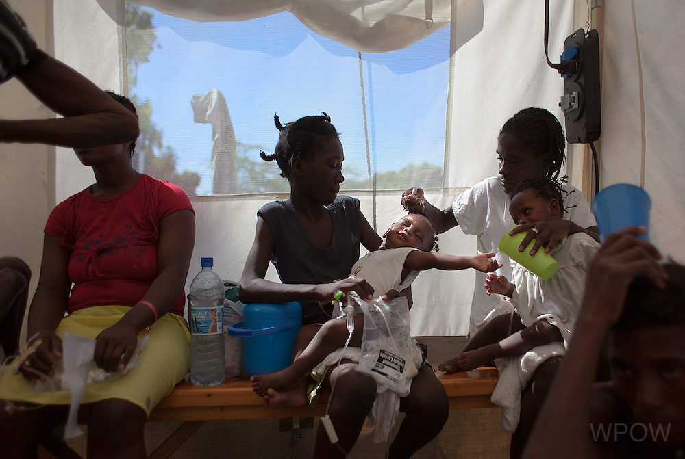 A pair of 15-month-old twins with cholera are held by their mother, right, and sister, center, as they receive IV drips in the intake tent at a cholera clinic set up by Medecins Sans Frontieres in the Tabarre neighborhood of Port-au-Prince, Haiti, November 19, 2010. (photo by Allison Shelley)