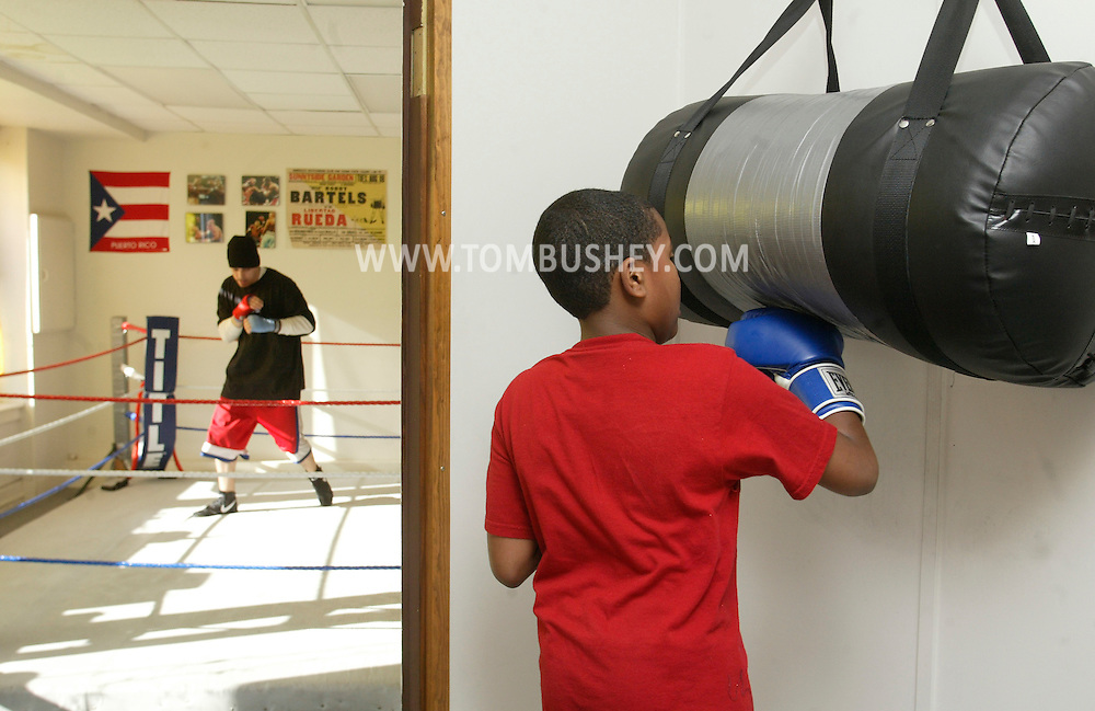 Jourdon Gonzalez, 10, hits the bag while another boxer works out in the ring at the Orange County Boxing Club in Middletown on April 19, 2007.